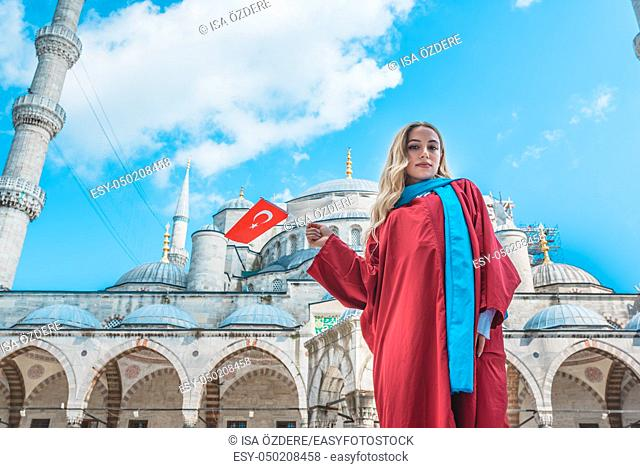 Attractive beautiful girl with covered clothes hold Turkish flag in front of Sultan Ahmet Mosque in Istanbul,Turkey. Travel Concept