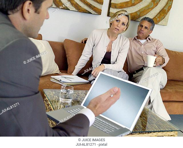 Couple on sofa talking to businessman with laptop