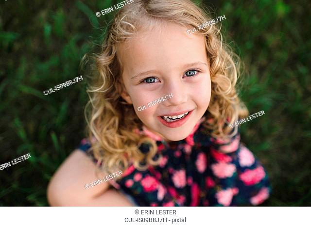 Overhead portrait of blond haired girl on grass