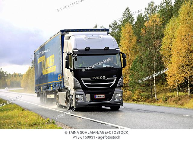 Raasepori, Finland - October 7, 2017: New Iveco Stralis XP truck pulls trailer along wet highway on rainy day of autumn in South of Finland