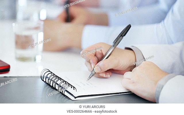 Closeup footage of the hands of a businessperson writing in a notebook and then panning down to end with someone writing in a diary
