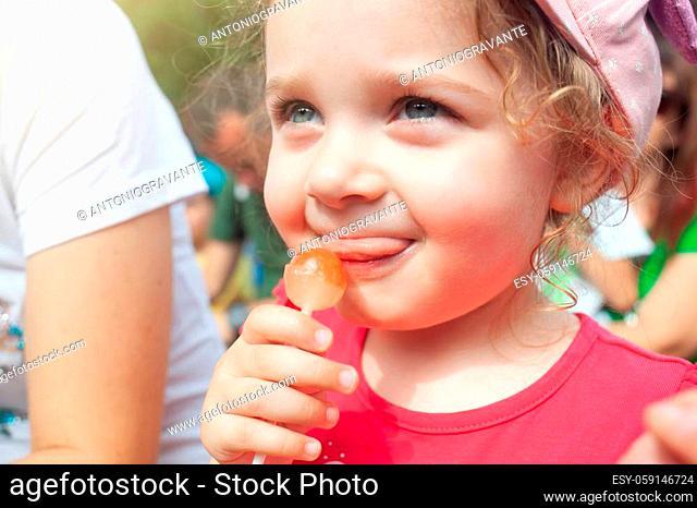 Cute little girl holding in hand a cherry lollipop