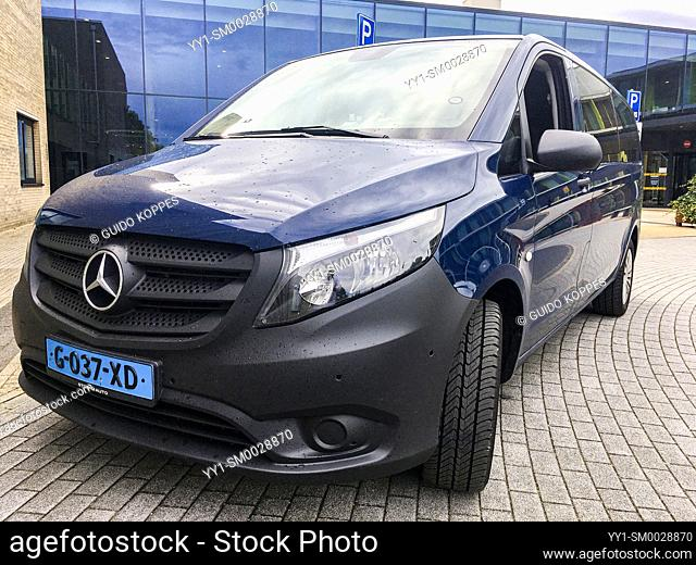 Tilburg, Netherlands. Mercedes-Benz Taxi Cab Van pared outside a large hospital's main entrace waiting for custoemrs and passengers