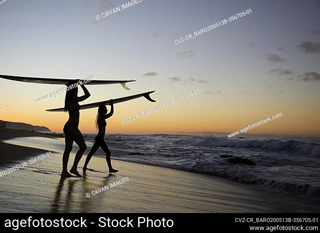 Girls paddling out for Sunset Surf on the North Shore in Hawaii