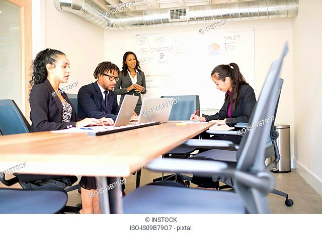 Businessman and businesswomen, in office meeting, using laptops