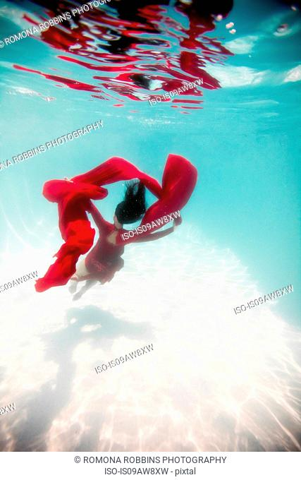 Woman wearing red dress,draped in red fabric, floating underwater