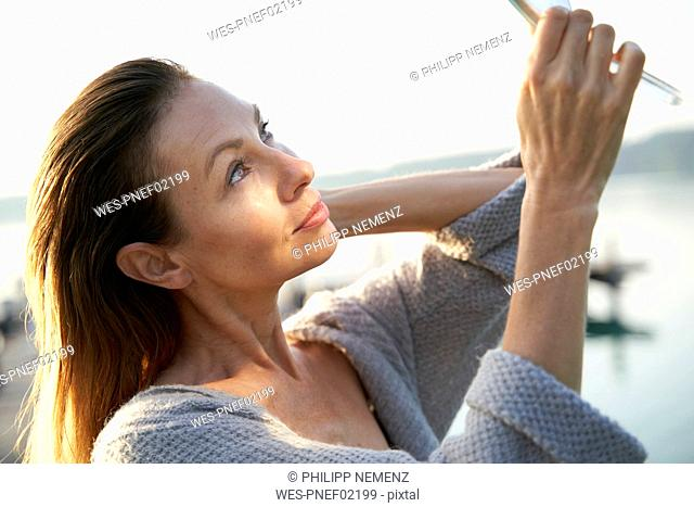 Mature woman looking in hand mirror at a lake