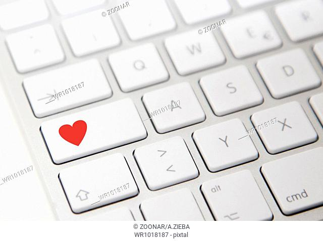 White computer keyboard with red heart button