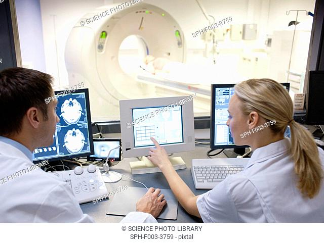 CT scanning. Radiographers taking a computed tomography CT scan of a patient