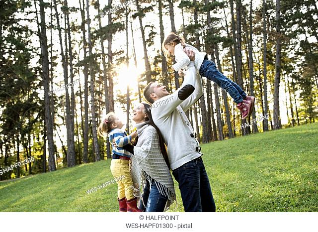 Playful family with two girls in forest