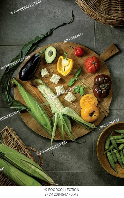 Fresh garden vegetables and corn on the cob on a wooden plate