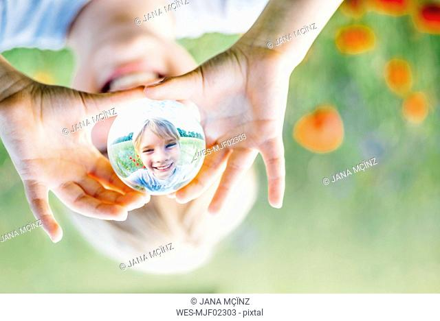 Reflection of smiling boy holding tansparent sphere in poppy field