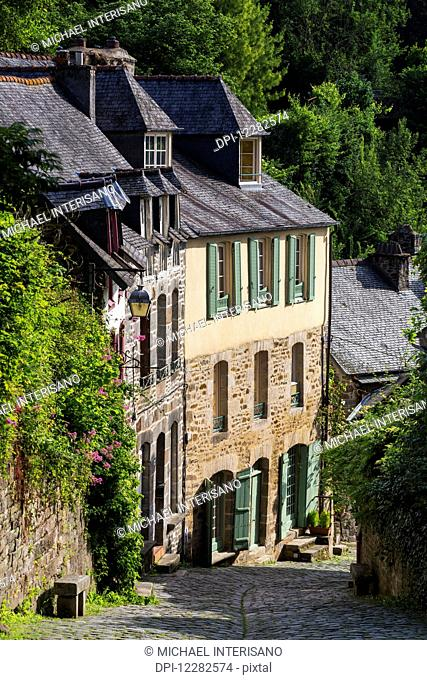 Old stone buildings with green shutters down a cobblestone road; Dinan, Brittany, France