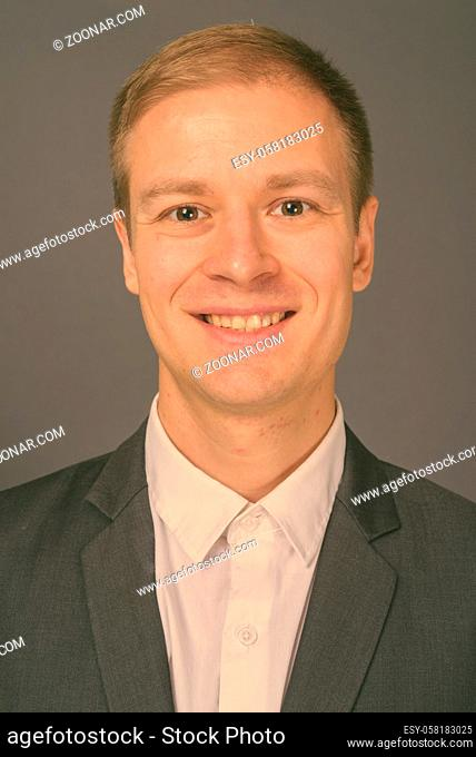 Studio shot of young handsome businessman against gray background