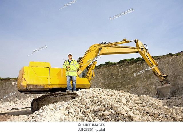 Construction worker standing on bulldozer in rock pit