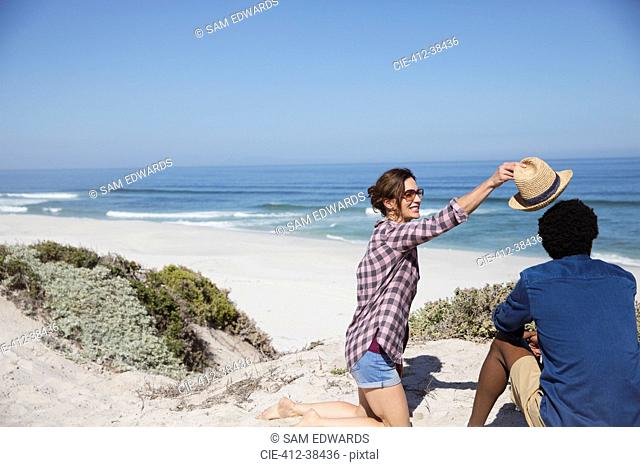 Woman placing hat on boyfriend on sunny summer ocean beach