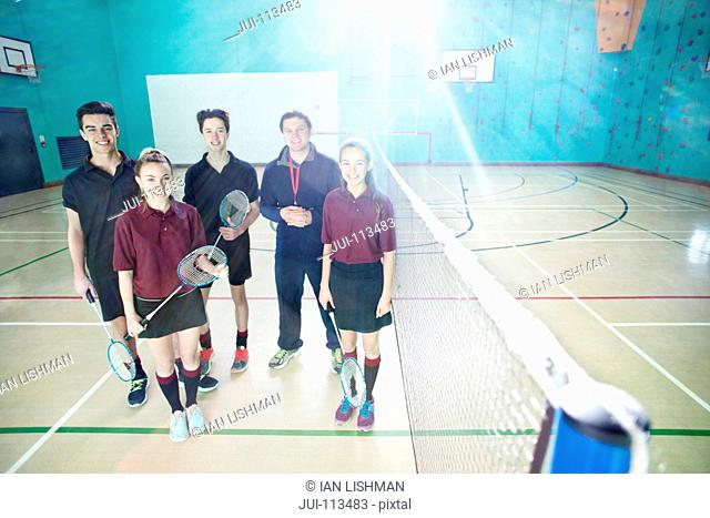 Portrait smiling gym teacher and high school students at badminton net in gym