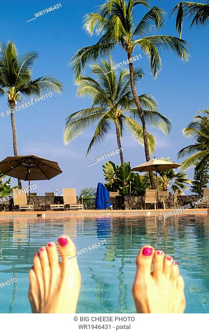 Woman's feet in front of a tropical swimming pool