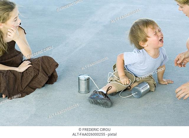 Little boy holding tin can phone, having tantrum, mother and sister watching