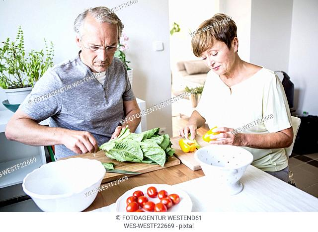 Senior couple in kitchen preparing salad together