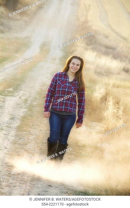 A happy teen girl walking on a rural dirt road