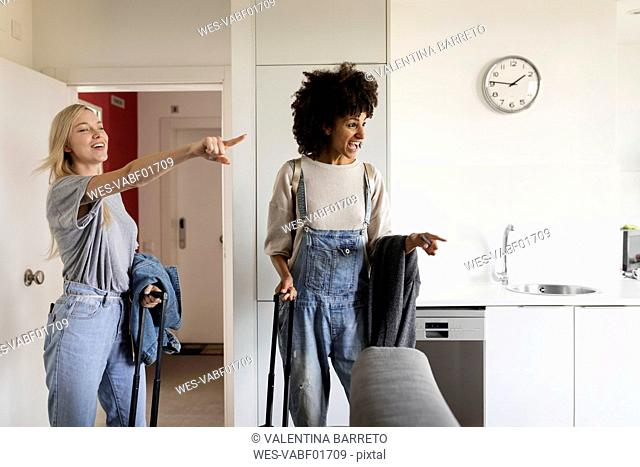 Two excited women with baggage arriving in accomodation