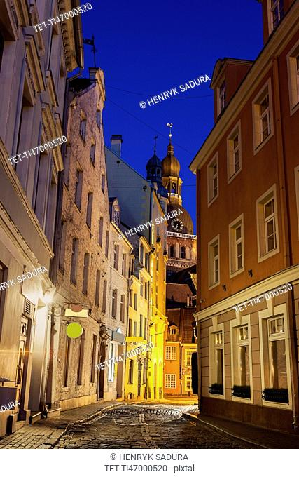 View of illuminated street in old town and Riga Cathedral at dusk