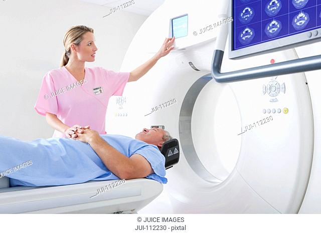 Technician nurse comforting patient at CT scanner in hospital