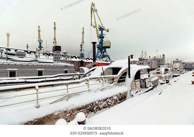 Night view of harbor cranes on the waterfront of the port covered with snow. Abandoned ships moored at the berth