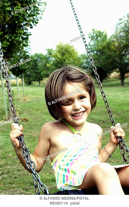 Smiling little girl playing on a swing