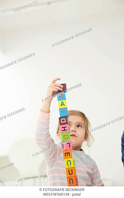 Germany, Munich , Girl playing with wooden blocks