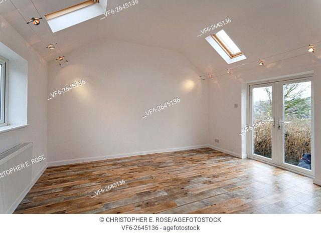 A large new unoccupied white painted high ceilinged empty room with Velux skylights