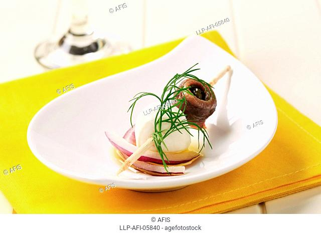 Mozzarella cheese and rolled anchovy on a stick