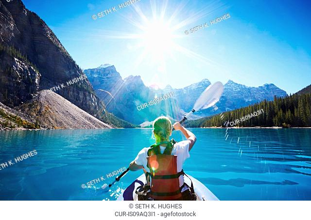 Mid adult woman kayaking, Moraine Lake, Alberta, Canada