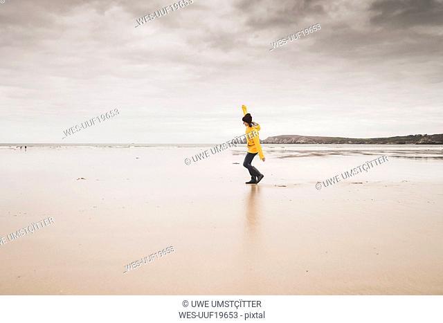 Young woman wearing yellow rain jacket at the beach, Bretagne, France