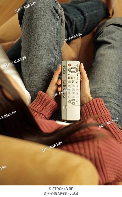 Woman with a Remote Control in her Hand sitting next to her Partner in an Armchair - Togetherness - Living Room - Home