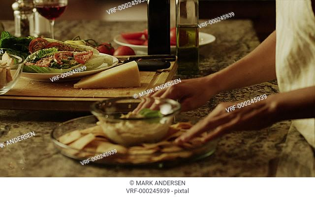 Close up panning shot of woman carrying salad and appetizer in kitchen / Cedar Hills, Utah, United States
