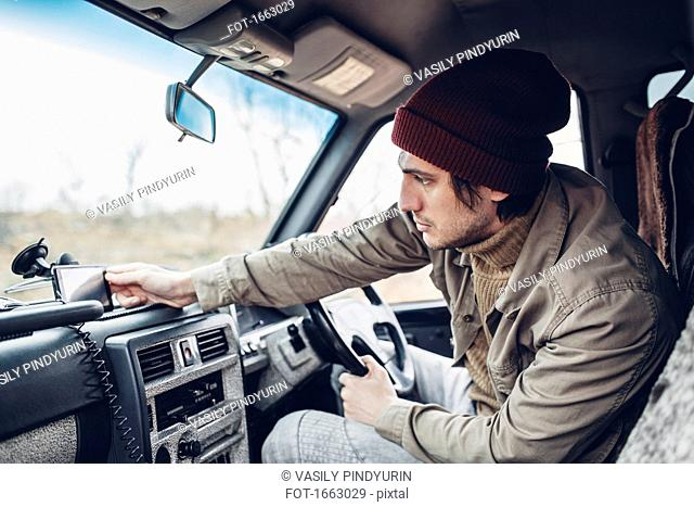 Man wearing knit hat and adjusting smart phone on dashboard of sports utility vehicle