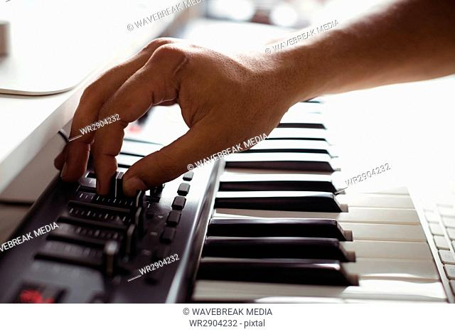 Hand of male audio engineer using sound mixer
