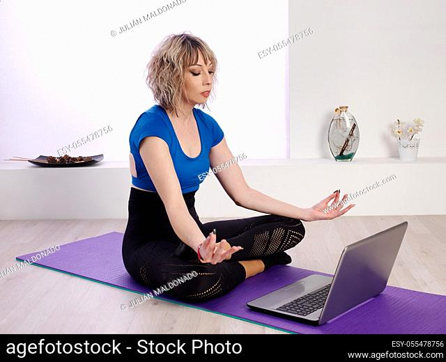 Pretty young woman consulting different Yoga exercises on the Internet in an online class