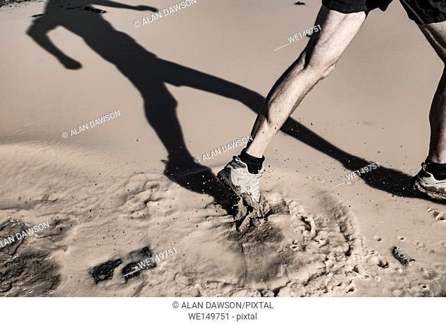 Man running through muddy puddle