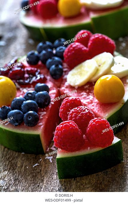 Fruitcake made of watermelon garnished with various fruits sprinkled with coconut flakes