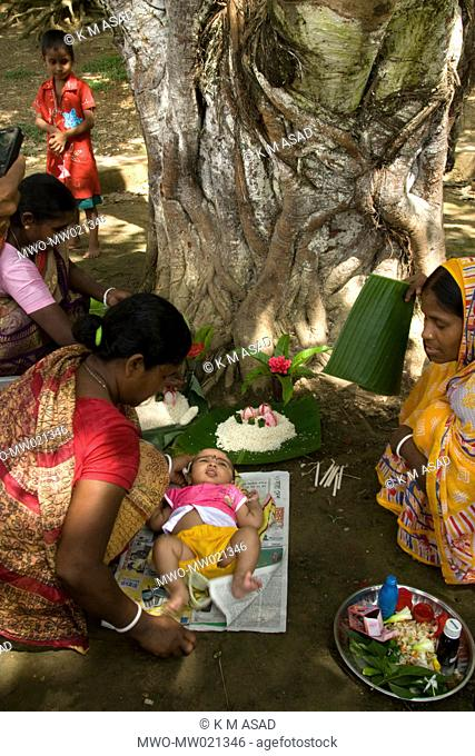 A mother performs religious rites for her child on Parbarana Purnima, a Buddhist holy day, in Bandarban, Bangladesh October 5, 2009