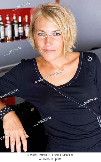 Portrait of woman posing by bar counter