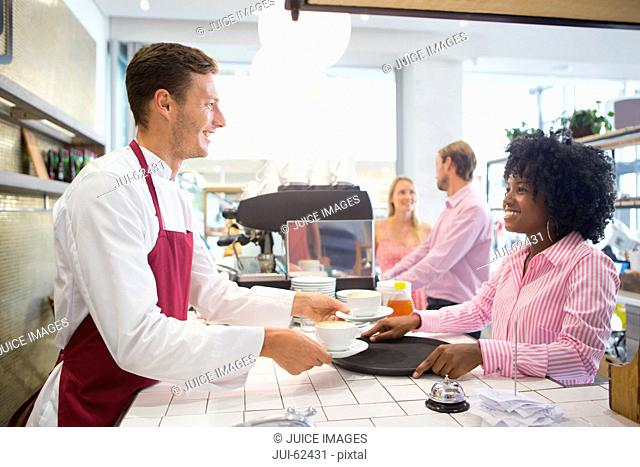Smiling waiter and waitress serving coffee in coffee shop
