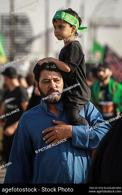 05 October 2020, Iraq, Karbala: A man carries his son on his shoulder during the Shia Muslims' march from Baghdad to visit the Husayn Mosque in Karbala on the...