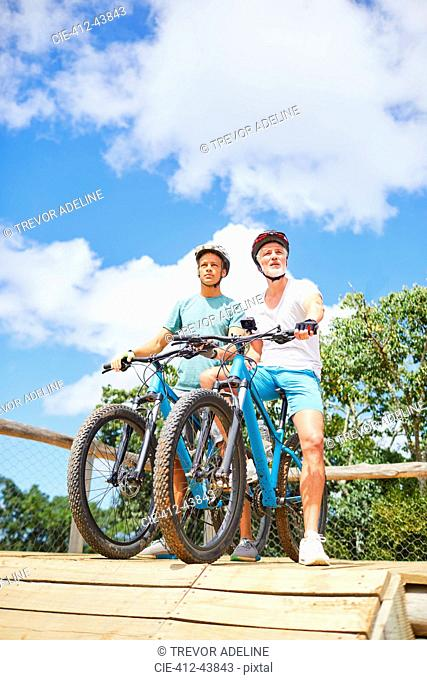 Father and son mountain biking at obstacle course