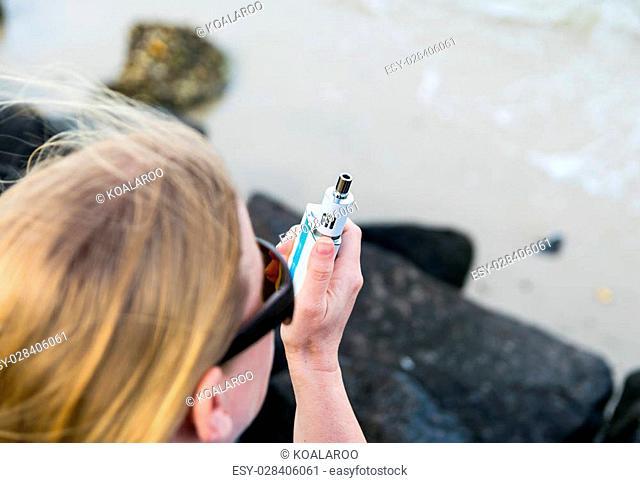 Woman smoking white Electronic Cigarette mod at the beach