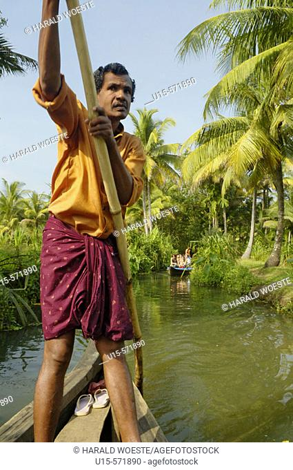 Indian boatman punting boat with tourists through the small canals of the backwaters in Kerala, India 2005