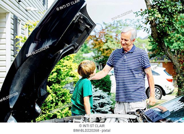 Caucasian grandfather and grandson repairing car in driveway
